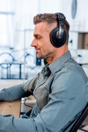 handsome cheerful man listening music in headphones in office