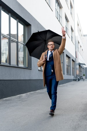 handsome businessman in glasses gesturing while running in beige coat with umbrella Stock Photo