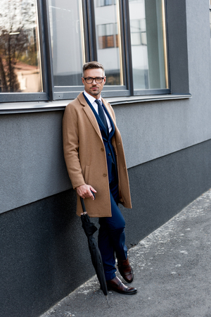 handsome businessman in glasses standing in beige coat with crossed legs and holding umbrella Stock Photo