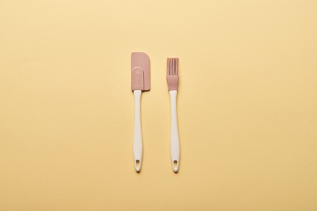 top view of silicone spatula and bakery brush on yellow background