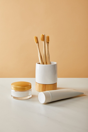 bamboo toothbrushes in holder, toothpaste in tube and cosmetic cream on white table and beige background Stock Photo