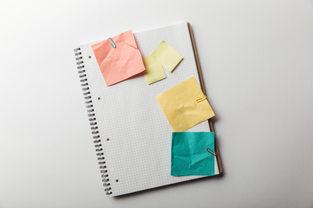 top view of notebook with blank squared page near crumpled sticky notes on white background