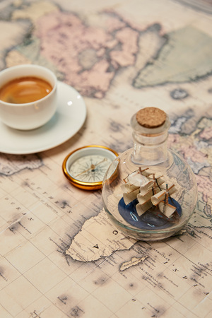 selective focus of coffee cup, compass and toy ship in glass bottle on map Banque d'images - 118534998
