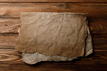 brown old parchment sheet lying on wooden background Stock Photo - 118535028
