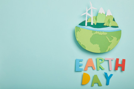 top view of paper cut planet with renewable energy sources and colorful letters on turquoise background, earth day concept