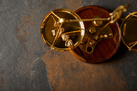 top view of golden stones on scales on grey and brown marble table