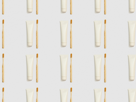 bamboo toothbrushes and toothpaste in tubes on grey background, seamless background pattern