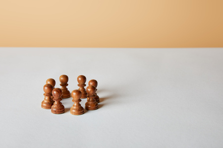 wooden pawn pieces on white table and beige background