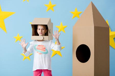 Interested kid in helmet waving hands near cardboard rocket on blue starry background 写真素材