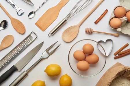 flat lay with metal and wooden cooking utensils and raw products on grey background