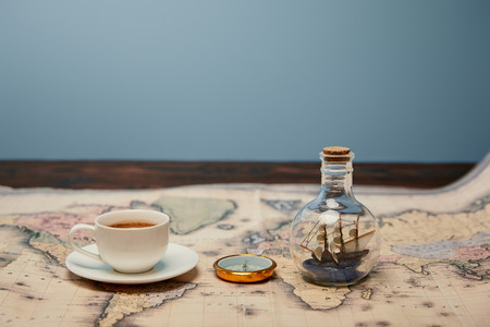 selective focus of coffee cup, compass and toy ship in glass bottle on map with copy space
