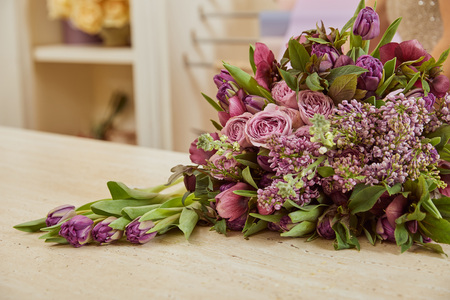 selective focus of purple tulips, peonies and lilac on surface