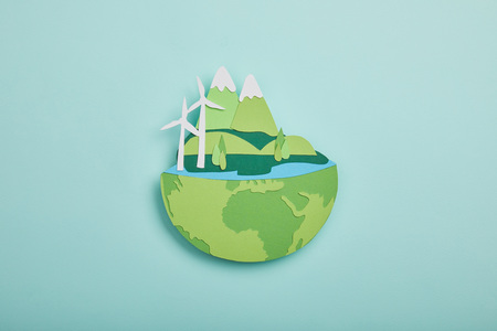 top view of paper cut planet with renewable energy sources on turquoise background, earth day concept