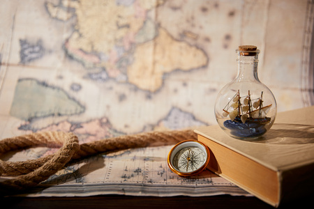Selective focus of toy ship in glass bottle, book, map and rope on table Foto de archivo - 118535569