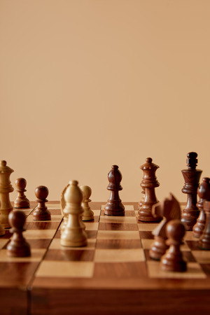 selective focus of chess on wooden chess board and beige background