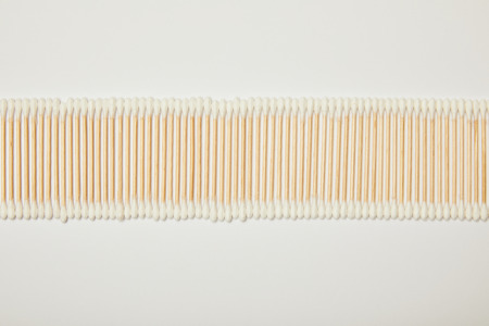 top view of cotton ear sticks laid out horizontally on white background