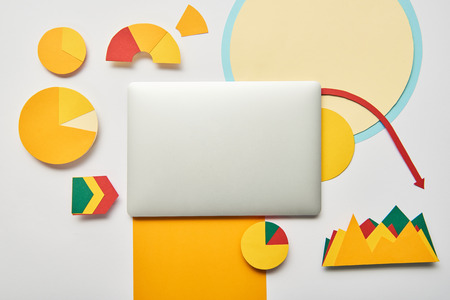 top view of laptop with paper charts and graphs, pointers, sheet of paper on white background Stock Photo