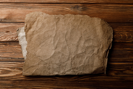 brown aged parchment sheet lying on wooden background