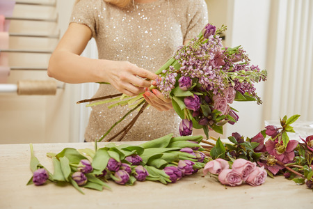 partial view of florist making bouquet of tulips, peonies and lilac at flower shop
