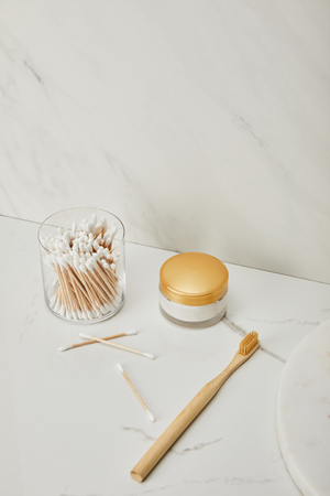 ear sticks in glass, cosmetic cream and bamboo toothbrush on white marble background