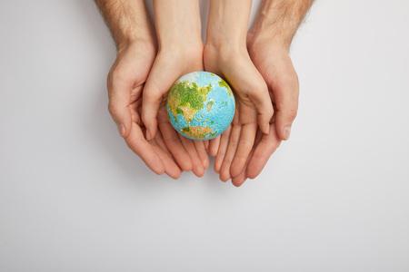 Vista superior del hombre y la mujer sosteniendo el modelo del planeta sobre fondo gris, concepto del día de la tierra