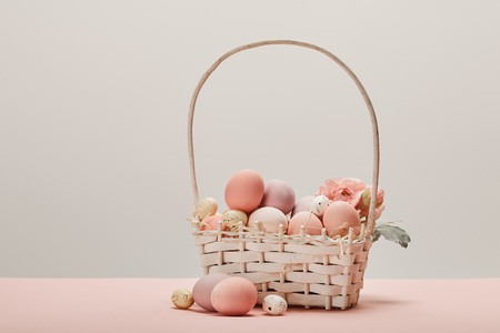 eater chicken and quail eggs in straw basket with flower on grey background