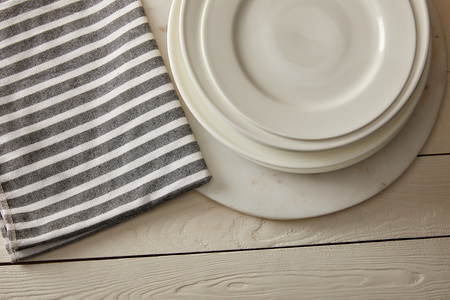 top view of stacked plates and striped cotton towel on white wooden surface