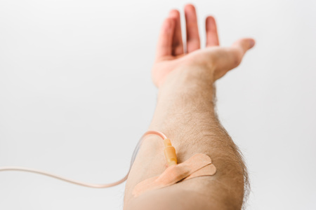 Partial view of blood donor with catheter and plasters on grey background, blood donation concept