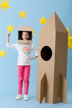 Inspired kid in helmet gesturing near cardboard rocket on blue starry background Banco de Imagens