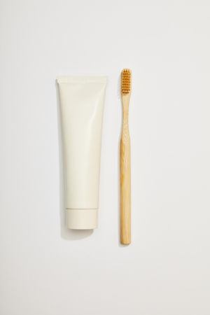top view of bamboo toothpaste in tube and toothbrush on white background