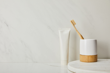 holder with bamboo toothbrush and toothpaste in tube on white marble background 스톡 콘텐츠