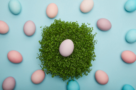 Top view of easter eggs on grass on blue background