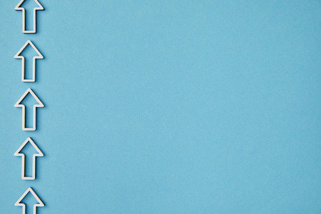 top view of vertical row white arrows on blue background