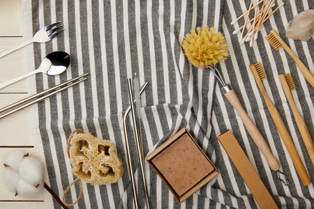 top view of cutlery, hygiene and care items on striped towel on white wooden surface, zero waste concept
