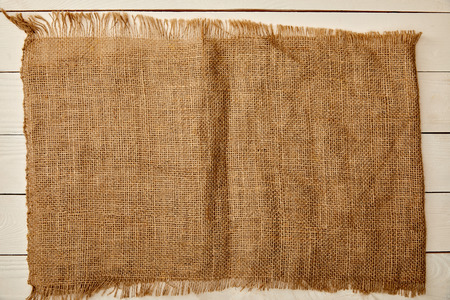 piece of brown sackcloth on white wooden surface