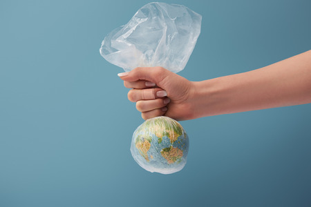 cropped view of woman holding globe in plastic clear bag on blue background