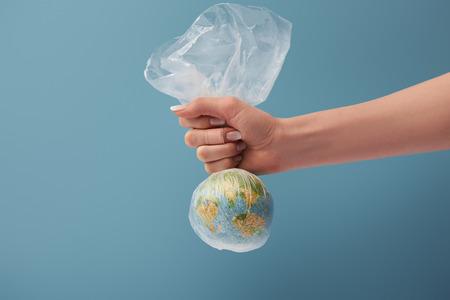 vue recadrée d'une femme tenant un globe dans un sac en plastique transparent sur fond bleu