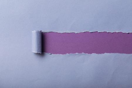 Papel azul rasgado con borde enrollado sobre fondo violeta