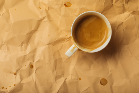 top view of cup with coffee on beige crumpled page 写真素材