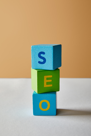seo lettering made of multicolored cubes on white table and beige background
