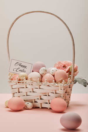easter chicken and quail eggs in straw basket with flower and card with happy easter lettering Foto de archivo - 118588892