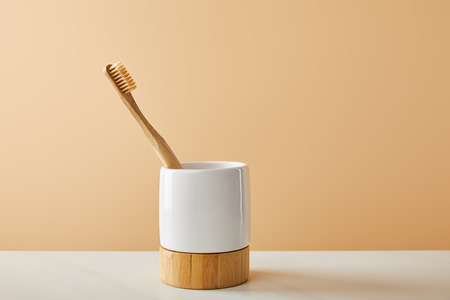 bamboo toothbrush in holder on white table and beige background Stock Photo