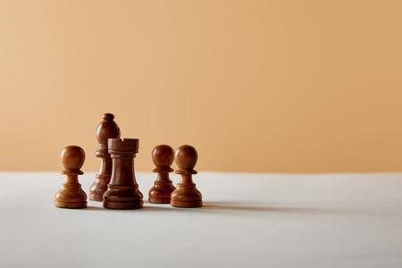 houten schaken op witte tafel en beige achtergrond Stockfoto