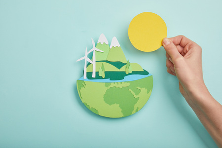 top view of woman holding paper cut sun and planet with renewable energy sources on turquoise background, earth day concept
