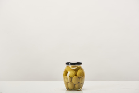 glass can of conserved olives on white surface