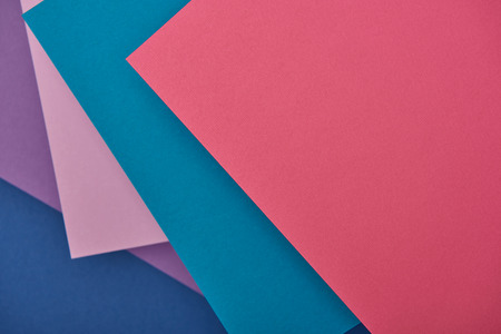 top view of lilac, blue and pink paper sheets with copy space