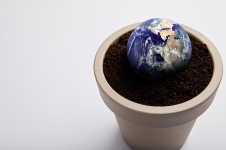planet model placed on flowerpot with soil, earth day concept
