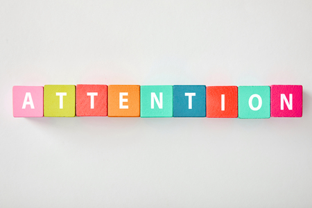top view of attention lettering made of multicolored blocks on grey background