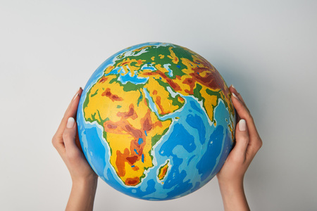 cropped view of woman holding globe on white background