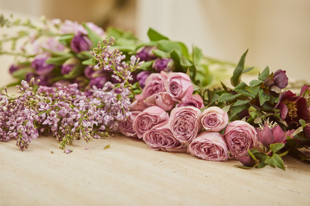 purple tulips, peonies and lilac on table at flower shop